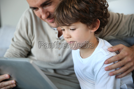 father and son playing with digital
