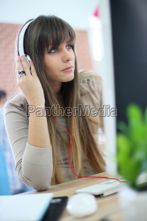 young woman at work using headphones