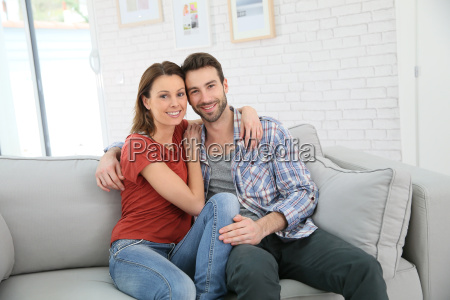 cheerful young couple relaxing in sofa