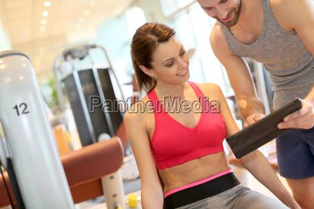 fitness girl con allenatore impostazione programma