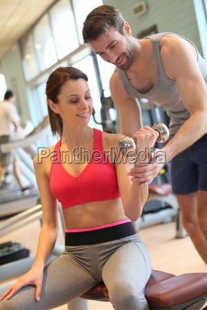 fitness maedchen mit trainer trainiert