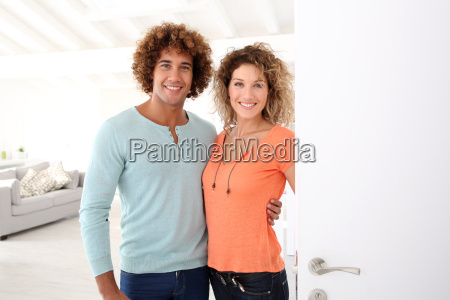 cheerful couple opening new home entrance