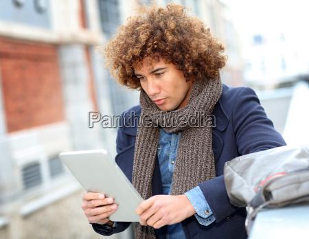 attractive man using digital tablet in