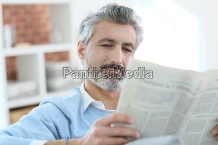 aeltere menschen liest zeitung im sofa