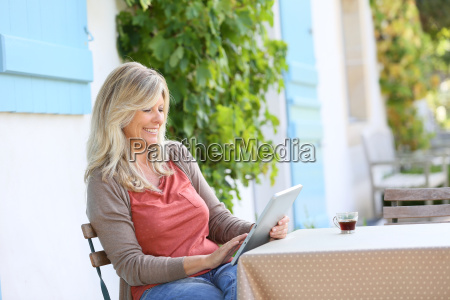 mature woman sitting in terrace and