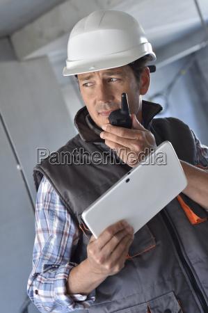 unternehmer auf der baustelle mit walkie