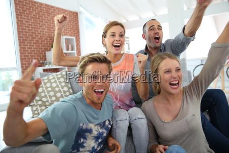 mitbewohner in der wohnung beobachten fussballspiel