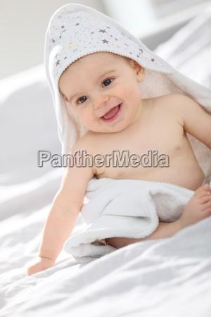 baby withbath handtuch ueber ihn