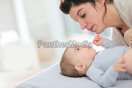 mama kuschelt baby junge auf wickeltisch
