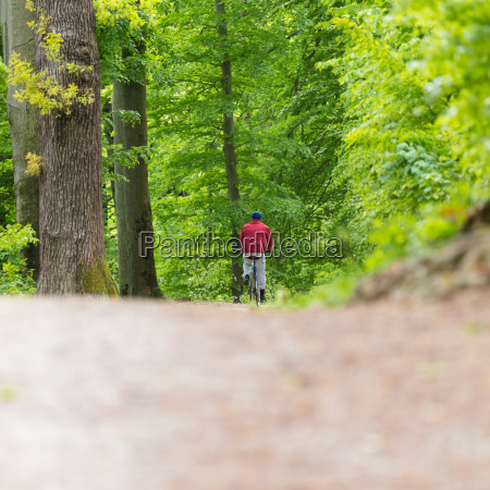 cyclist riding bycicle on forest trail