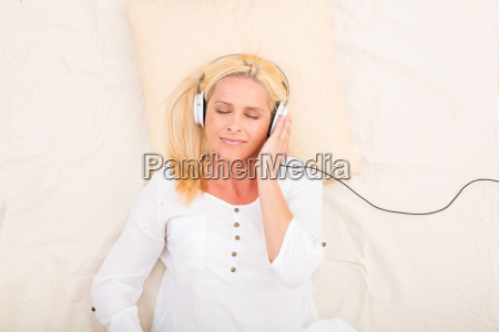 woman with headphones and tablet in