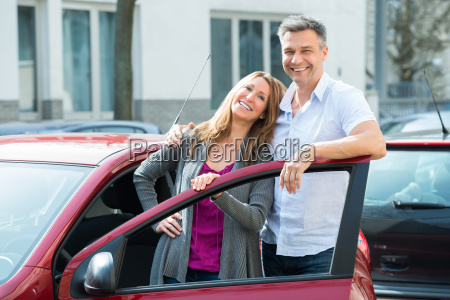 happy couple with new red car
