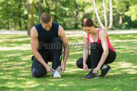 young couple tying shoes