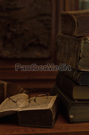 antique books with reading glasses