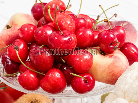cherries and peaches on white wooden