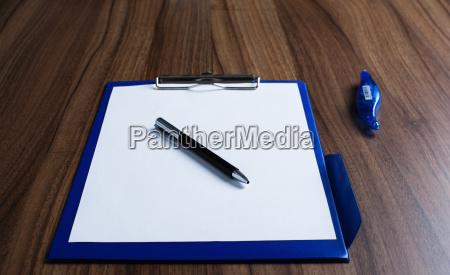 schreibtisch mit weissem blatt papier und