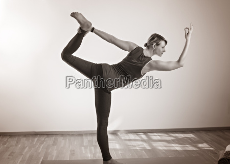 frau die yoga macht im stehen