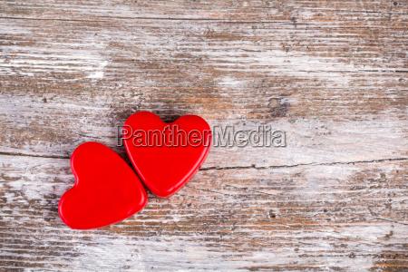 zwei rote herzen auf holz hintergrund