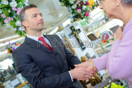 funeral director haende mit aelteren frau