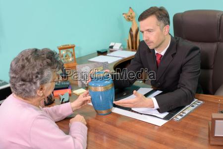 director funerario con mujer mirando urna