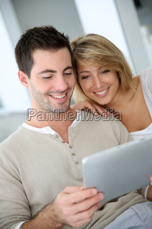 cheerful couple using digital tablet at