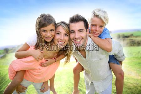 eltern geben huckepack auf kinder