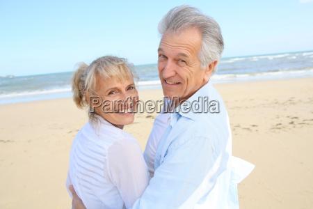 froehlich aeltere paare stehen am strand