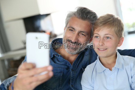 father and son taking picture of
