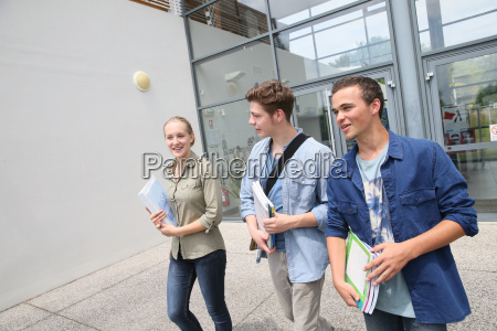 young students walking outside campus building