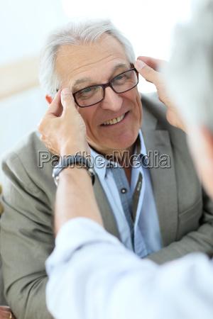 senior man trying new eyeglasses on