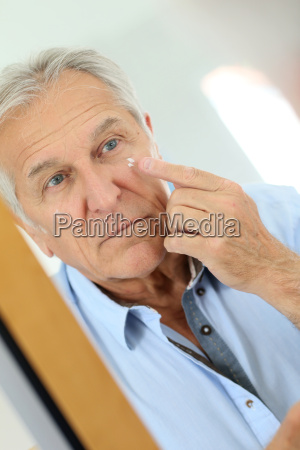 senior man applying anti aging lotion