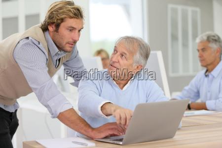 senior man attending business class with