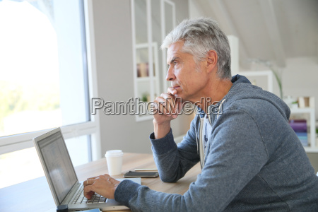 senior man working from home on