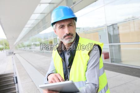 ingenieur mit schutzhelm mit tablette ausserhalb