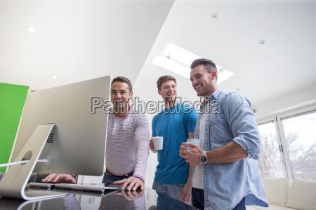 freunde versammeln sich um computer