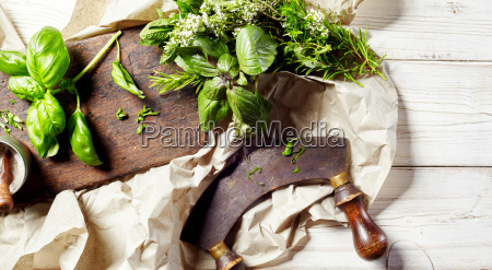 chopping assorted fresh herbs with a
