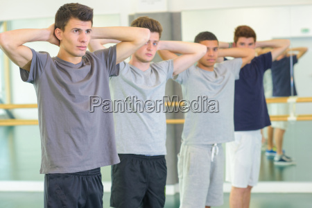 four young men exercising arms behind