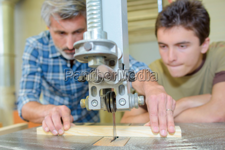 apprentice carpenter watching how to use