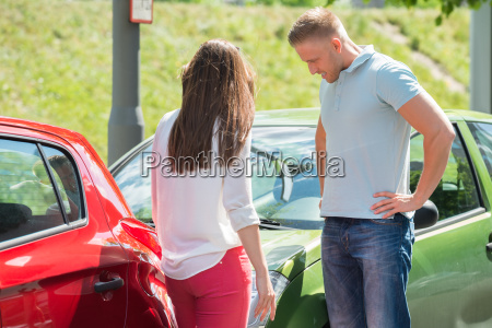 couple looking at broken down car