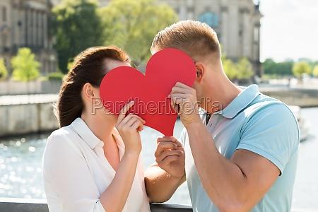 couple hiding behind heart shape