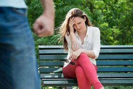 upset frau sitzt auf bank