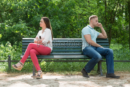 displeased couple sitting on bench