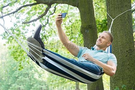 man lying in hammock taking picture