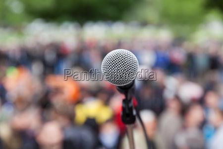 mikrofon im fokus gegen verwischt publikum