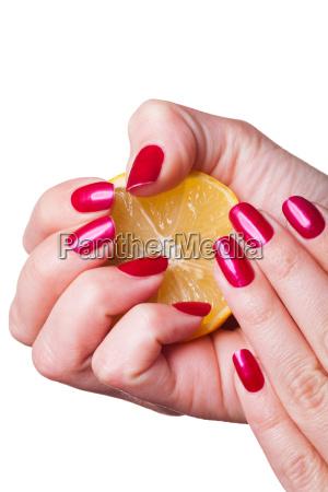 hand mit roten fingernaegeln zerdrueckt zitrone
