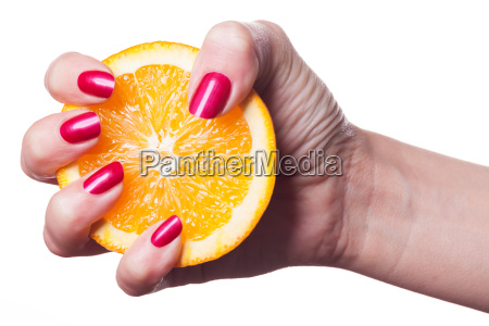 hand mit gepflegten fingernaegeln und orange