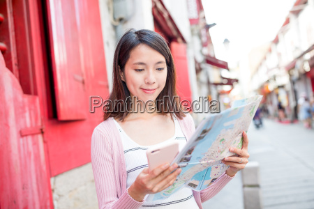 woman reading on city map in