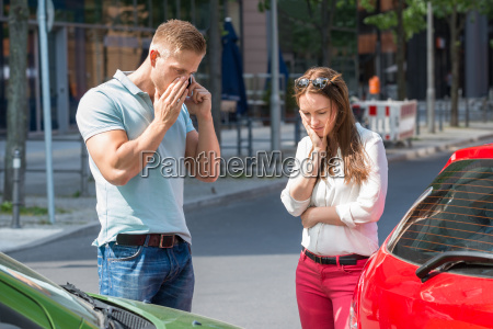 man on mobile phone after car