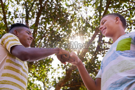 african and caucasian boys joining hands