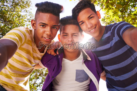 multiethnic group of teenagers embracing smiling